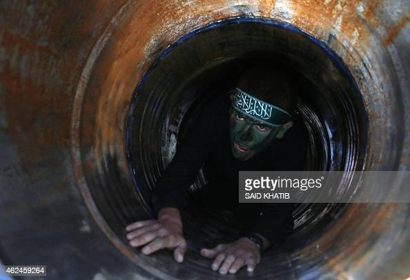 A Palestinian youth crawls in a tunnel during a graduation ceremony for a training camp run by the Hamas movement on January 29 2015 in Khan Yunis in...