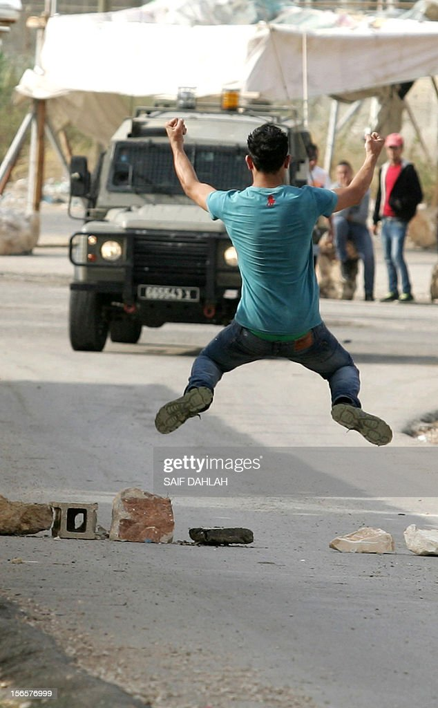 A Palestinian youth gestures at Israeli soldiers during clashes in the Jalama checkpoint in the West Bank near Jenin city, on November 17, 2012. Israeli strikes on Gaza killed at least eight Palestinians and destroyed the Hamas government headquarters as Israel called up thousands more reservists for a possible ground war.