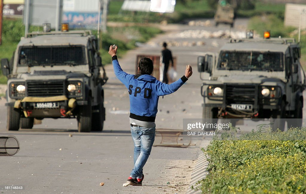 A Palestinian youth holding stones, gestures towards Israeli security forces during clashes at the entrance of the Jalama checkpoint, near the West Bank city of Jenin, on February 15, 2013.