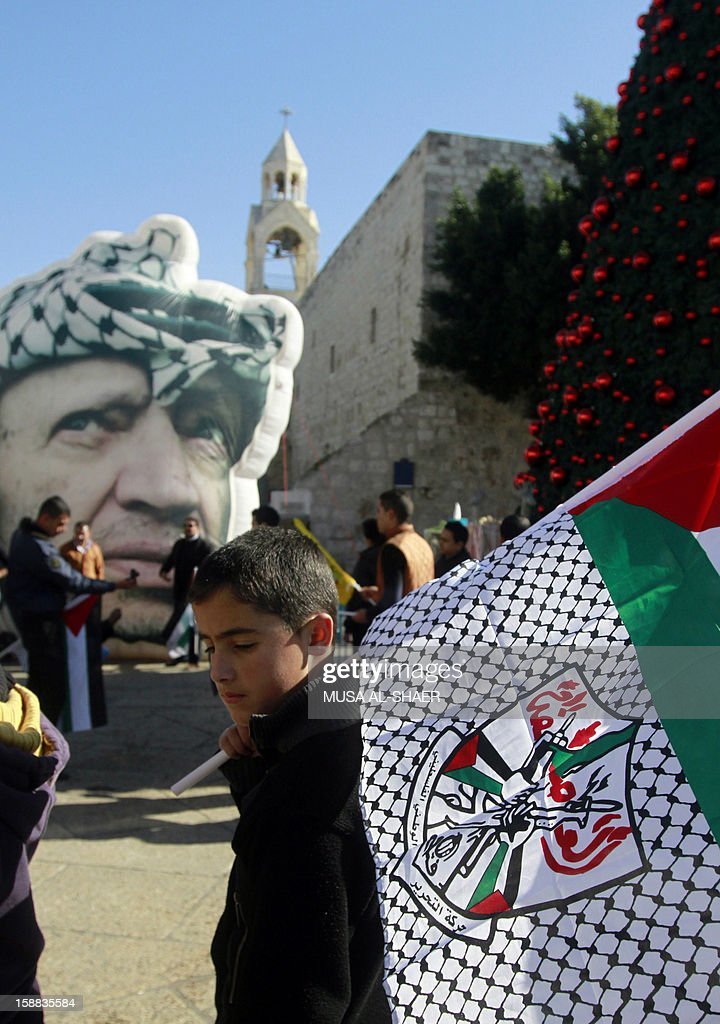 A Palestinian youth holds a flag bearing the Fatah movement's emblem near a giant portrait of late Palestinian leader Yasser Arafat (Back-L) in front of the Church of the Nativity in the West Bank city of Bethlehem, on December 31, 2012, during celebrations marking the 48th anniversary of the movement's founding.