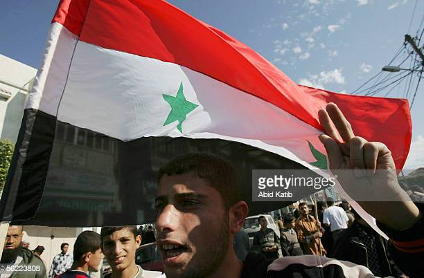 Palestinian youth holds a Syrian flag during a proSyrian demonstration on November 18 2005 in Gaza City Gaza Strip Hundreds of Palestinians...