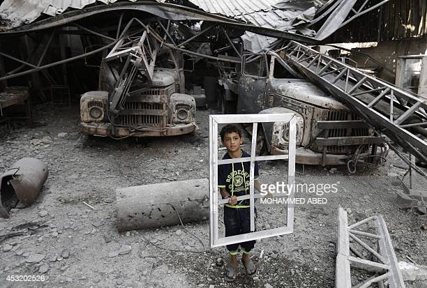 A Palestinian youth holds a window frame as he inspects a destroyed building in the AlShejaea neighbourhood of Gaza City on August 5 after a 72hour...