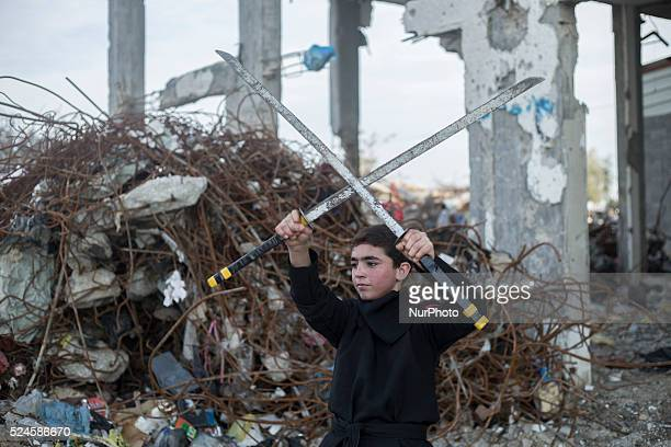 A Palestinian youth holds swords as he practice Ninja Martial Arts skills between the rubble of destroyed houses at Al Nada towers northern the Gaza...