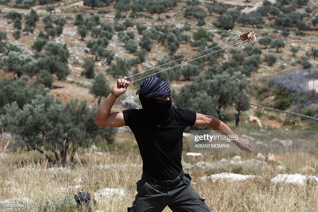 A Palestinian youth hurls a stone towards Israeli forces during clashes following a protest against land confiscation and Israeli settlements in the West bank village of Bilin on May 07, 2010. President Shimon Peres told visiting US envoy George Mitchell that security must be a top issue in Washington's efforts to launch indirect peace talks between Israel and the Palestinians.