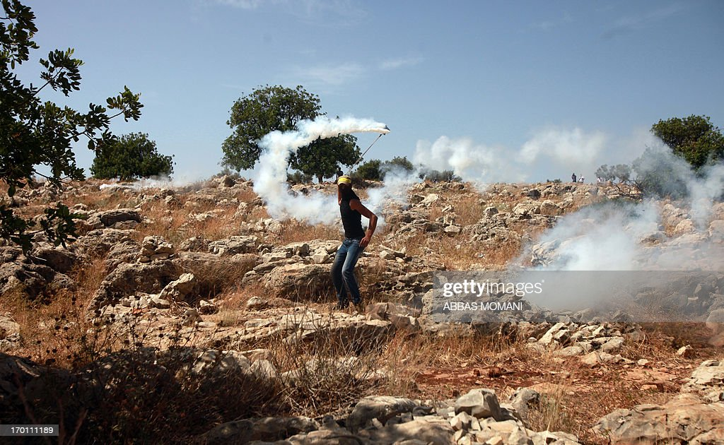 A Palestinian youth hurls a tear gas canister back towards Israeli security forces during clashes following a demonstration against Israeli settlements and its separation wall, in the West Bank village of Nilin on June, 7, 2013.