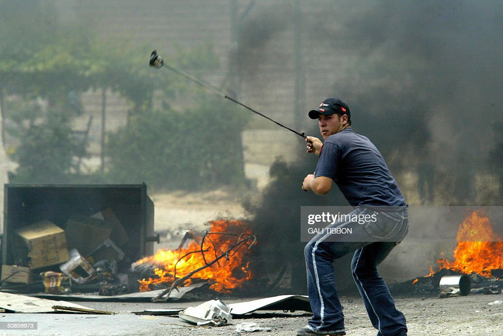 A Palestinian youth hurls stones at Israeli security forces during clashes in the West Bank village of Biddu 20 May 2004. A total of 41 Palestinians have been killed since the Israeli army launched its Rafah raid in the Gaza Strip early 18 May dubbed 'Operation Rainbow' and aimed at stopping arms smuggling from Egypt through cross-border tunnels.