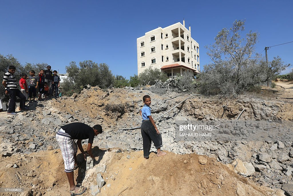 Palestinian youth inspect the damage following an Israeli air raid on al-Zawaida in the central Gaza strip early on June 24, 2013