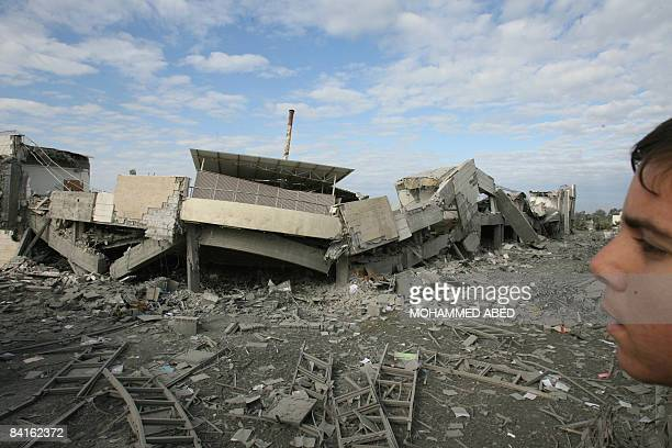 A Palestinian youth inspects the rubble following an Israeli air strike targeting the American International school of Gaza in Beit Lahia on January...