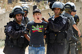 A Palestinian youth is arrested by Israeli security as bulldozers destroy a Palestinian home in Arab east Jerusalem's neighborhood of Beit Hanina on...