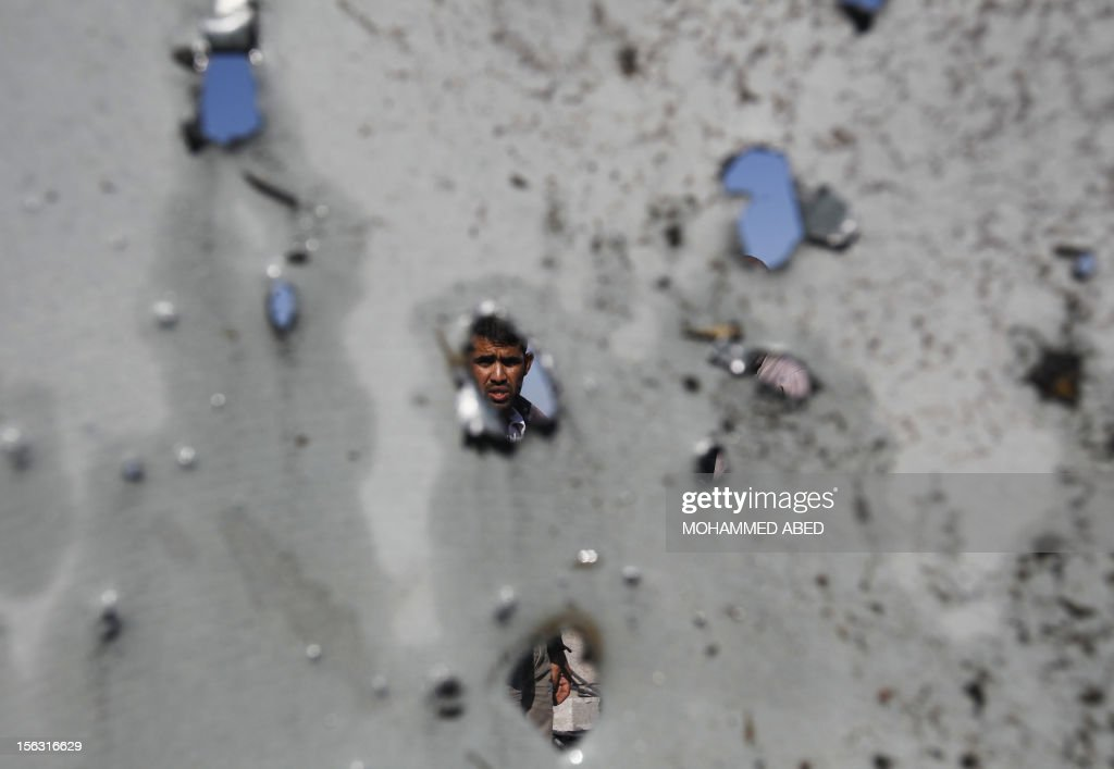 A Palestinian youth is seen through the shrapnel riddled ceiling of a house that was damaged following an Israeli air strike in the Jabalia refugee camp on November 13, 2012. Israeli Defence Minister Ehud Barak warned that a flare-up in violence with Gaza was 'not over,' after new rocket fire in the morning and Israeli strikes overnight.