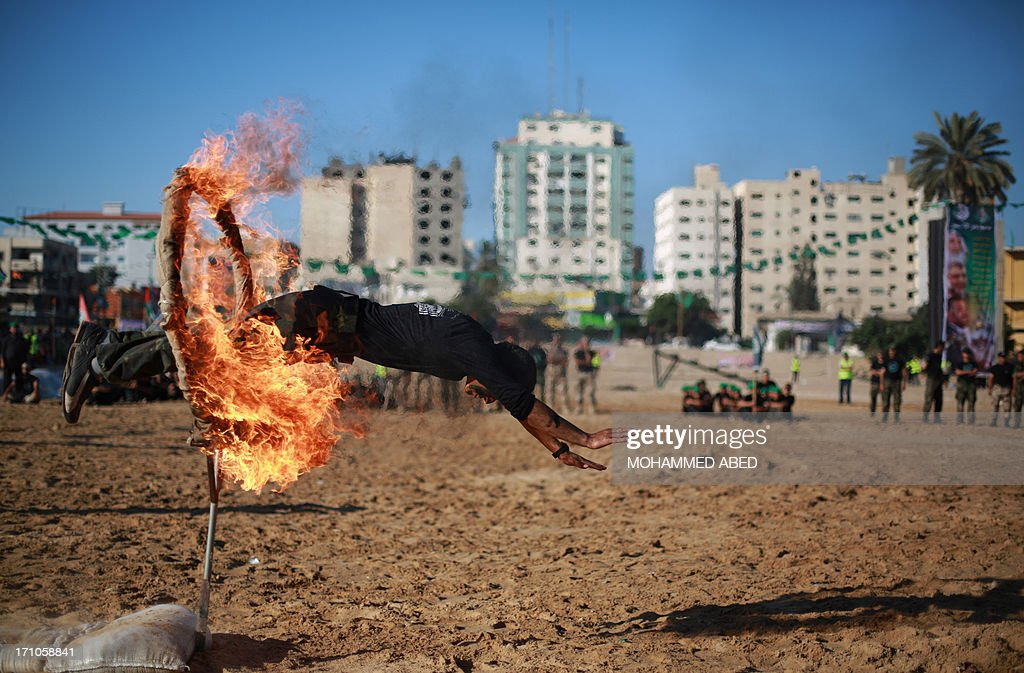 A Palestinian youth jumps through a ring of fire during a summer physical training camp run by Hamas in Gaza City on June 21, 2013.