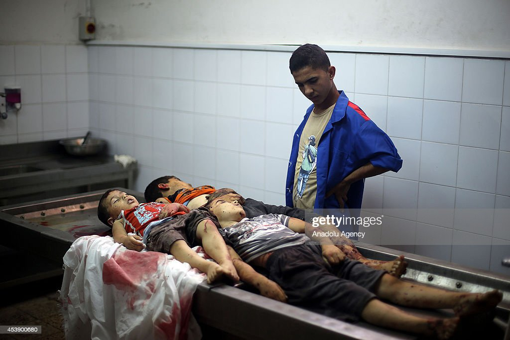 A Palestinian youth looks at the bodies of 3 Palestinian kids from the Al-Rifi family who were killed in an Israeli air strike, in the morgue of the Shifa hospital in Gaza on August 21, 2014. Three children, aged 7, 8 and 11, and a 35-year-old man from the Al-Rifi family were killed in a fresh Israeli airstrike in the Gaza Strip on Thursday, according to Health Ministry spokesman Ashraf al-Qodra. The latest fatalities, he said, bring the total number of Palestinians killed in relentless Israeli attacks on the Gaza Strip to 2072 since hostilities began on July 7.