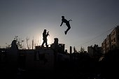 TOPSHOT Palestinian youth members of a Gazan martial art group perform their ninjalike skills at ruins of a house that was destroyed in the 2014 war...