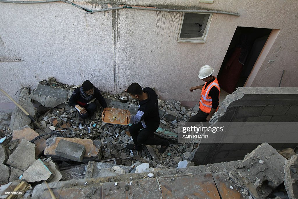 A Palestinian youth offers an elderly man tea as he sits amid the rubble in his damaged house following overnight Israeli air strikes on the southern Gaza Strip town of Rafah on November 20, 2012. The Israeli military said it attacked about 100 targets in the coastal strip during the night, using aircraft, warships and artillery.