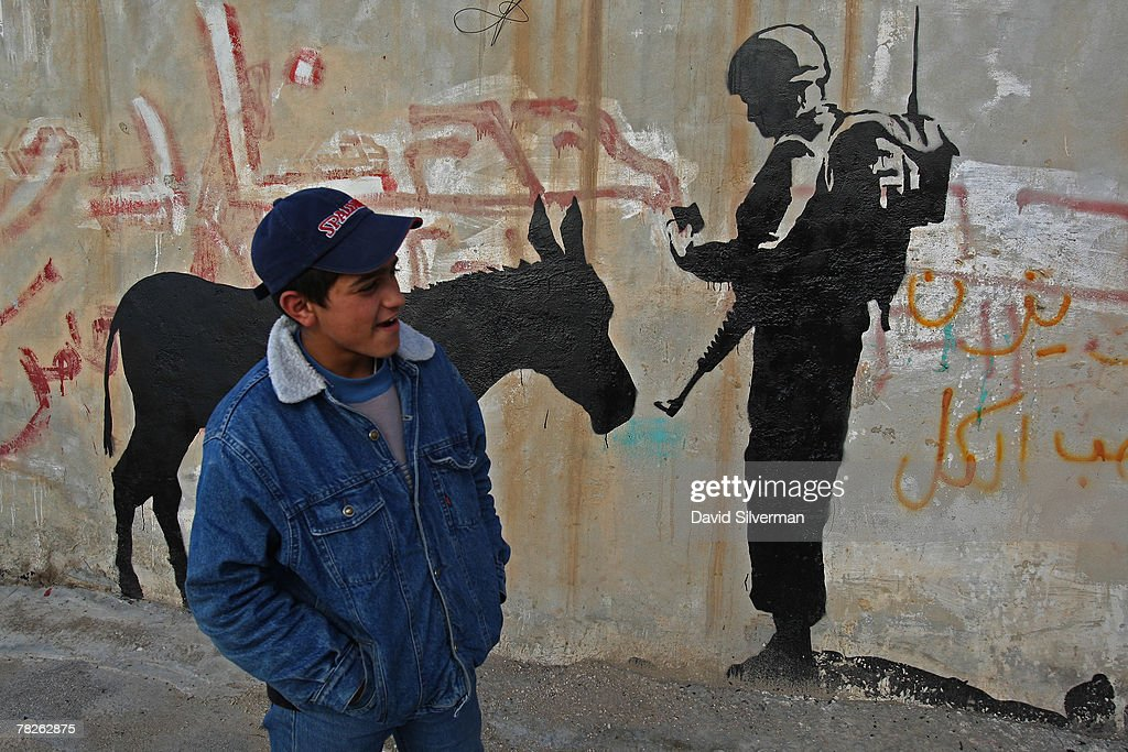 A Palestinian youth passes a wall painting by elusive British graffiti artist Banksy December 5, 2007 on a shop wall in the biblical city of Bethlehem in the West Bank. The Bristol-born artist has adorned Israel's West Bank separation barrier and Bethlehem walls with new images, including this one of a soldier checking a donkey's identity documents, a soldier being frisked by a young girl and a dove wearing a flak jacket. His works, along with those of other international artists, are part of an exhibition called Santa's Ghetto.