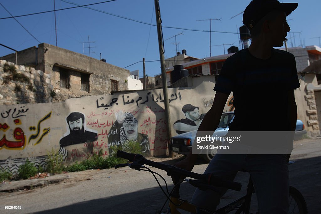 A Palestinian youth passes nationalist grafitti on April 6, 2010 in Jenin, West Bank. The Cinema Jenin team of German professionals, local Palestinian staff and foreign volunteers, with funding from the German government, the Roger Waters foundation and other sponsors, are tuning the city's run-down cinema into a modern cinematheque. Their stated aim is to encourage a culture of cinema-going for both the population of Jenin and its refugee camp, and to provide the city with a sustainable cultural centre while fostering principles of peaceful conflict resolution, co-existence and acceptance of others by denouncing all forms of violence and fanaticism.