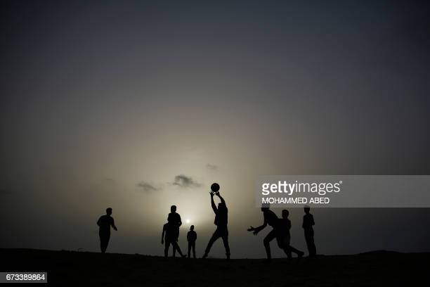 TOPSHOT Palestinian youth play volley ball as the sun sets in Gaza City on April 26 2017 / AFP PHOTO / MOHAMMED ABED