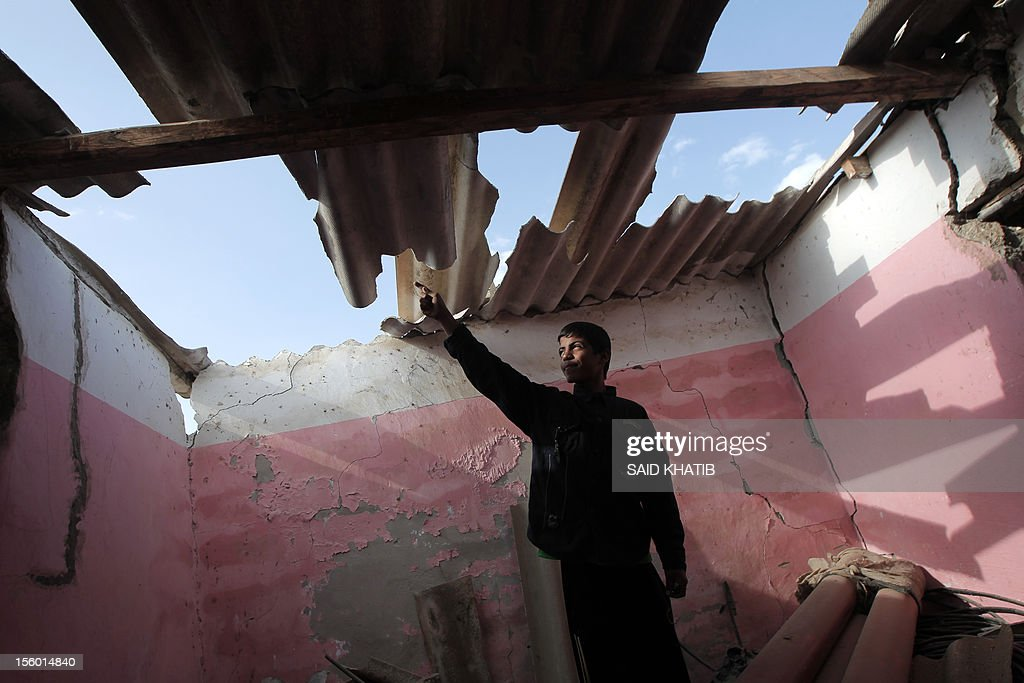 A Palestinian youth points to the damaged roof of a building following an Israeli military air strike in Rafah town in the southern Gaza Strip, on November 11, 2012. The flare-up which began November 10, was one of the most serious since Israel's devastating 22-day operation in the Gaza Strip over New Year 2009, has culminated in six Palestinians being killed and 32 injured by Israeli strikes after militants fired on an Israeli jeep, wounding four soldiers, medics and witnesses said. AFP PHOTO/ SAID KHATIB
