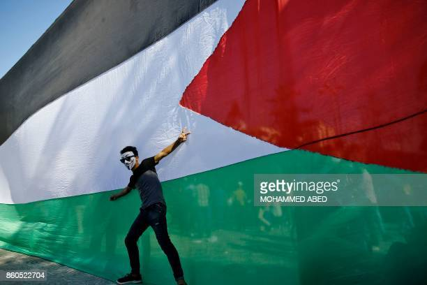 Palestinian youth poses in front of his national flag during celebrations in Gaza City after rival Palestinian factions Hamas and Fatah reached an...