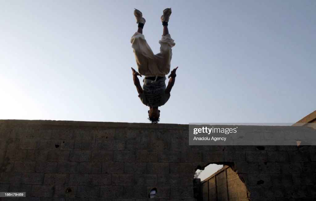 A Palestinian youth practices his parkour skills in Gaza City on October 31, 2013. Parkour, French slang for the art of moving, is a physical activity that maximizes the body's efficiency with the aim of overcoming obstacles such as buildings, rails, and even people.