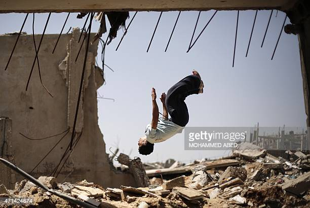 A Palestinian youth practices his Parkour skills in the ruins of buildings on April 28 2015 in the eastern Gaza City neighbourhood of Shejaiya which...
