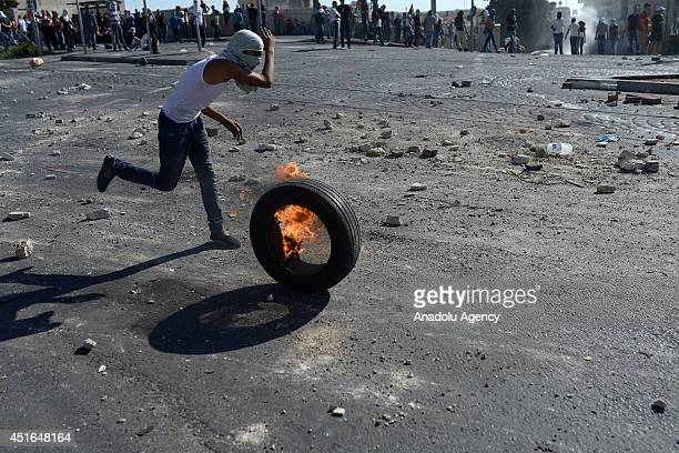 Palestinian youth rolls a burning tire towards Israeli security forces during the clashes over the abduction and killing of a Palestinian teen by...