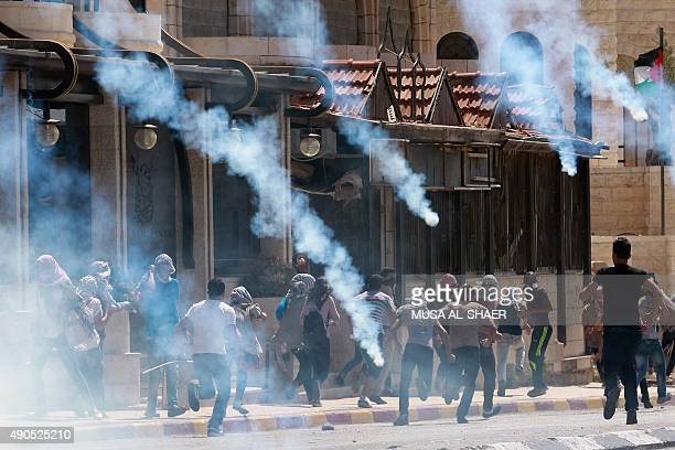 Palestinian youth run from tear gas fired by Israeli security forces during clashes over the AlAqsa mosque compound on September 29 at the main...
