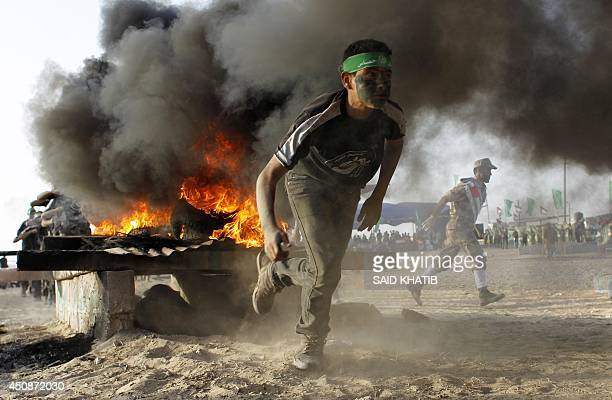 A Palestinian youth runs as he takes part in militaryinspired exercises during a summer camp organised by the Islamist movement Hamas on June 19 2014...