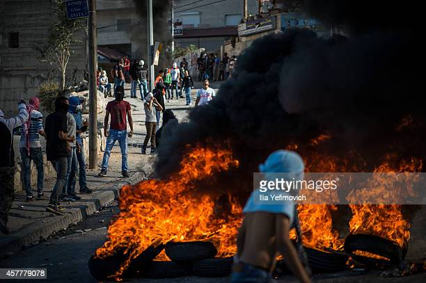 Palestinian youth seen burning tires during clashes with Israeli police in Issawia on October 24 2014 in Jerusalem Israel Clashes have continued two...