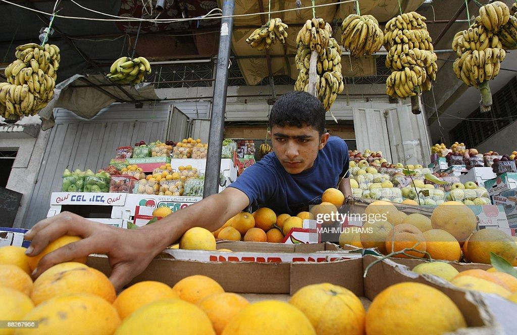 A Palestinian youth sells fruits at a shop in Jabalia refugee camp northern Gaza Strip on June 6 2009 AFP PHOTO/MAHMUD HAMS