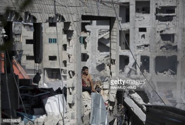 A Palestinian youth sits in a destroyed building in part of Gaza City's alTufah neighbourhood as the fragile ceasefire in the Gaza Strip entered a...