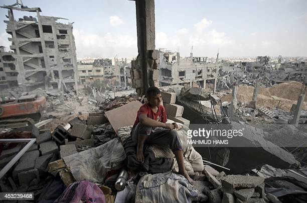 A Palestinian youth sits on the rubble of a destroyed building in part of Gaza City's alTufah neighbourhood as the fragile ceasefire in the Gaza...