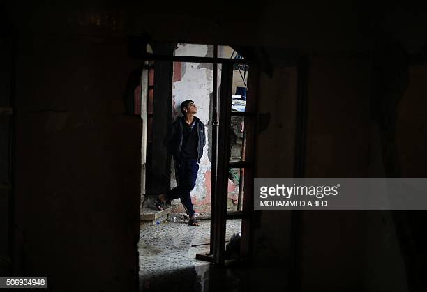 Palestinian youth stands outside his damaged house on January 26 during a winter storm in Beit Hanoun in the northern Gaza Strip His home was damaged...