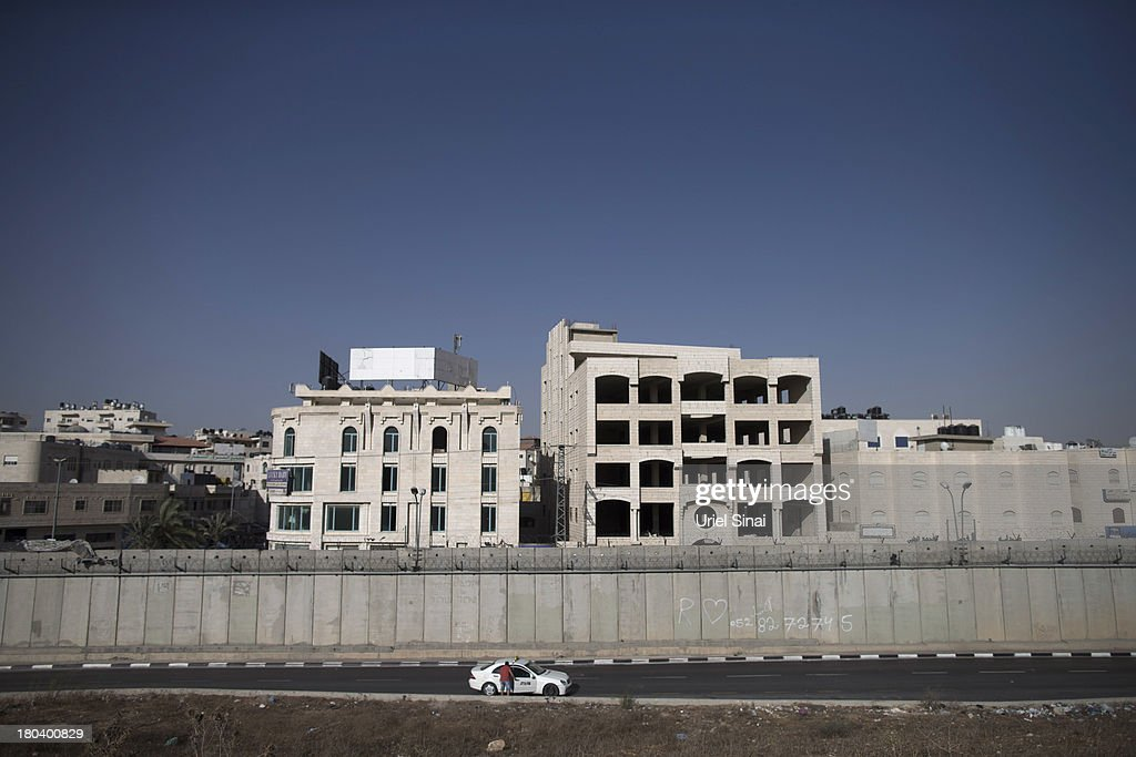 A Palestinian youth stops a taxi along the Israeli West Bank barrier on the outskirts of Jerusalem on September 12, 2013 in Aram, West Bank. The twenty-year anniversary of the Oslo Accord, which was to set up a framework for peace between Israel and Palestine, will be marked on September 13.