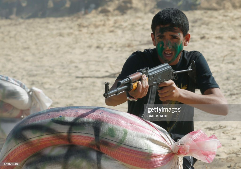 A Palestinian youth takes part in a military-style summer camp being held by the Islamic Jihad movement during the youngsters' summer school vacation in Rafah town, in the southern Gaza Strip, on June 12, 2013. Thousands of youngsters between the age of six and 16, can participate in the summer camp where they receive military as well as religious training.