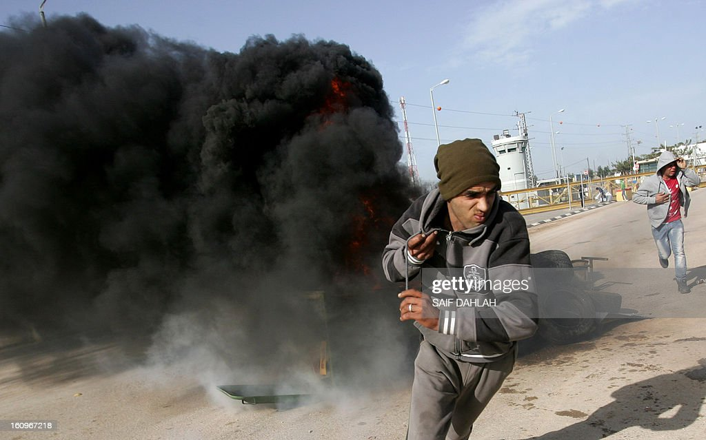 A Palestinian youth takes takes cover from the fumes of burning tyres during clashes with Israeli soldiers at the Jalama checkpoint near the West Bank city of Jenin on February 8, 2013. AFP PHOTO/SAIF DAHLAH