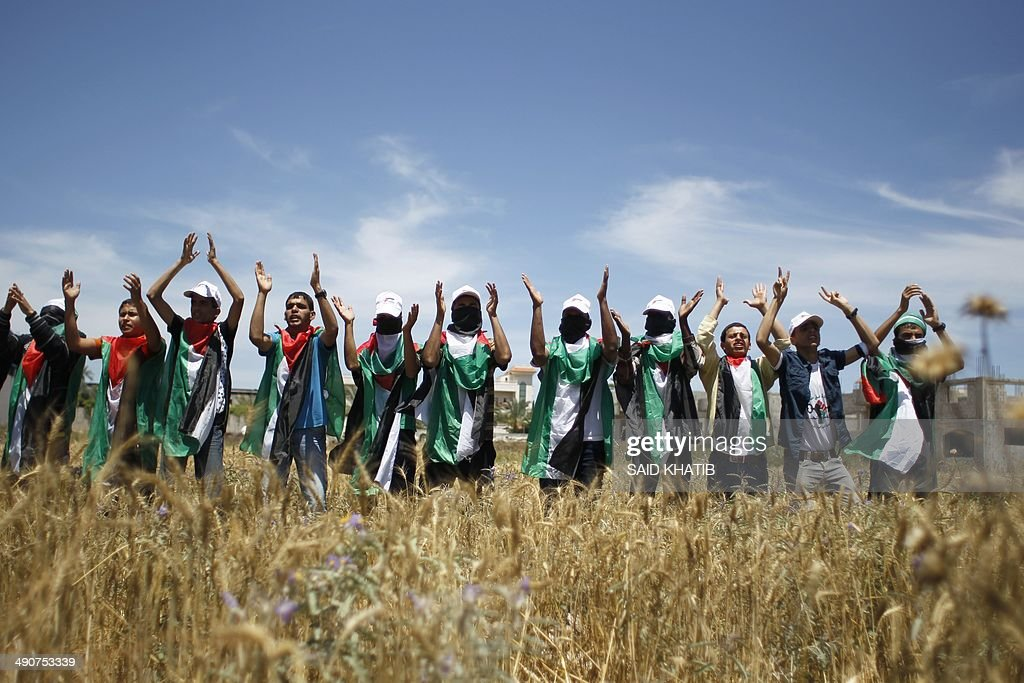Palestinian youth, their bodies draped in the national flag gather in a field near Gaza City on May 15, 2014, as they mark Nakba Day. Palestinians are marking 'Nakba day' which means in Arabic 'catastrophe' in reference to the birth of the state of Israel 66-years-ago in British-mandate Palestine, which led to the displacement of hundreds of thousands of Palestinians who either fled or were driven out of their homes during the 1948 war over Israel's creation.