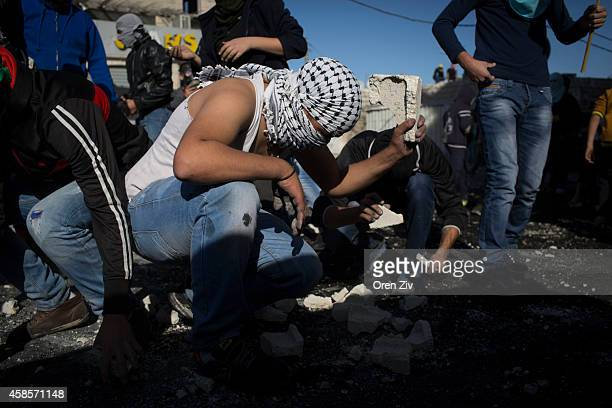 Palestinian youth throw rocks at police after noon prayer on November 7 2014 in Jerusalem Israel A Palestinian resident of Shuafat refugee camp was...