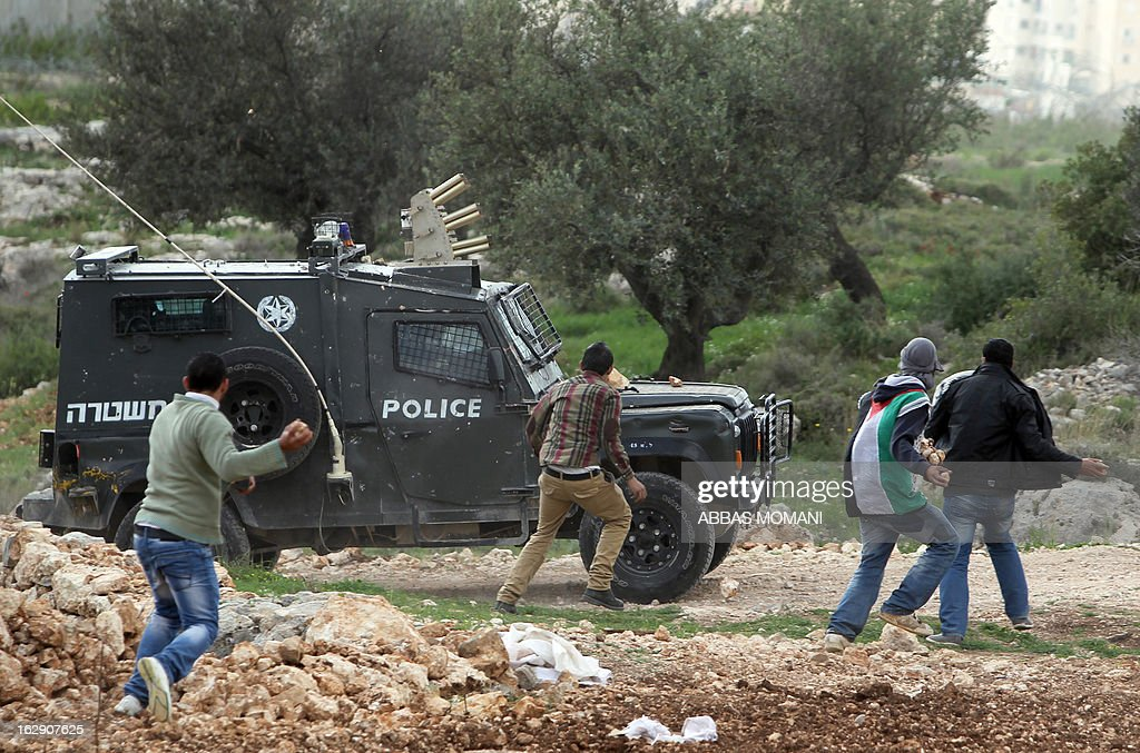 Palestinian youth throw stones at an Israeli police jeep during clashes between hundreds of youths and Israeli security in the West Bank village of Bilin on March 1, 2013, following a large march which headed towards Israel's controversial separation barrier in support of Palestinian prisoners held in Israeli jails, and marking eight years of weekly protests which kicked off in February 2005, against Israel's barrier which encroaches on Palestinian villagers' lands.