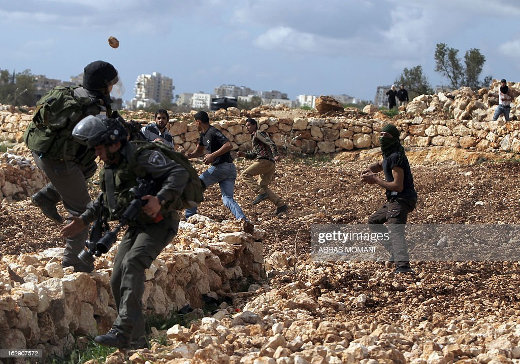 Palestinian youth throw stones towards Israeli border guards during clashes between hundreds of youths and Israeli security in the West Bank village of Bilin on March 1, 2013, following a large march which headed towards Israel's controversial separation barrier in support of Palestinian prisoners held in Israeli jails, and marking eight years of weekly protests which kicked off in February 2005, against Israel's barrier which encroaches on Palestinian villagers' lands.