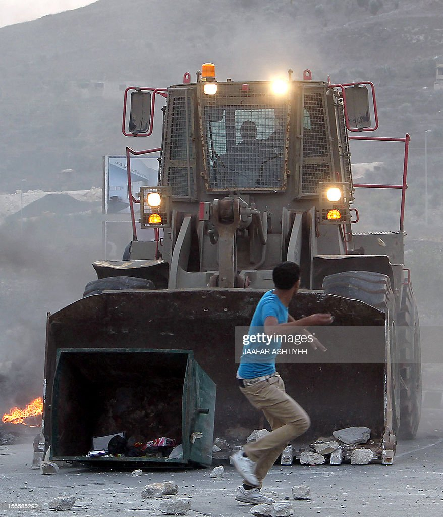 A Palestinian youth throws a rock towards an Israeli maned bulldozer during protests at the Hawara checkpoint in the occupied West Bank city of Nablus, on November 17, 2012. Palestinians took to the streets to demonstrate against the Israeli military operation on the Gaza Strip which has seen some 40 people killed in the past 4 days including Palestinian children.