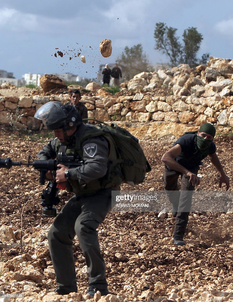 A Palestinian youth throws a stone at an Israeli border guard during clashes between hundreds of youths and Israeli security in the West Bank village of Bilin on March 1, 2013, following a large march which headed towards Israel's controversial separation barrier in support of Palestinian prisoners held in Israeli jails, and marking eight years of weekly protests which kicked off in February 2005, against Israel's barrier which encroaches on Palestinian villagers' lands. AFP PHOTO/ABBAS MOMANI