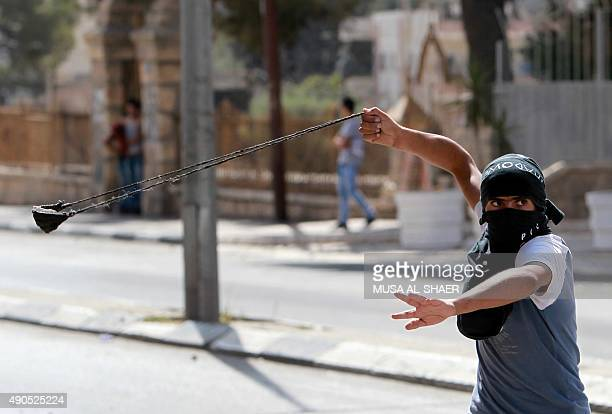 A Palestinian youth throws a stone during clashes against Israeli security forces over the AlAqsa mosque compound on September 29 at the main...