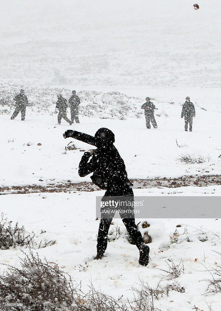 A Palestinian youth throws a stone towards Israeli forces under snowfall during clashes which broke out after Israeli settlers from the nearby Esh Kodesh settlement cut Palestinian farmers' olive trees on January 10, 2013 in village of Qusra, south of the city of Nablus. Israeli settlers opened fire in the northern West Bank wounding two Palestinians in separate incidents, Palestinian security forces and witnesses said. AFP PHOTO/JAAFAR ASHTIYEH