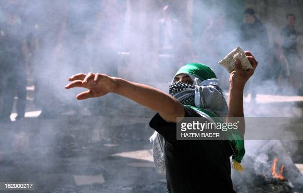 A Palestinian youth throws a stone towards Israeli soldiers during a protest in the West Bank city of Hebron on September 27 as Israeli security also...