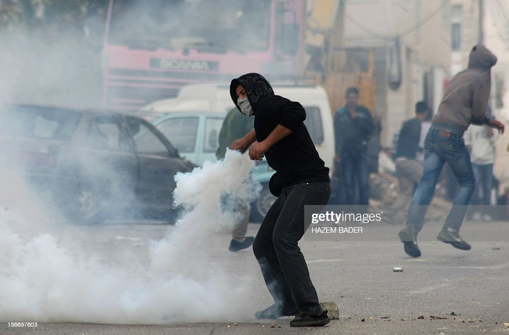 A Palestinian youth throws back a tear gas canister fired by Israeli forces during clashes in the Halhul village near the West Bank city of Hebron, on November 19, 2012, following a protest against the ongoing Israeli offensive on the Gaza Strip. Israeli air strikes across the Gaza Strip killed 13 people, raising the Palestinian death toll to 90 as Israel's relentless air campaign entered its sixth day.