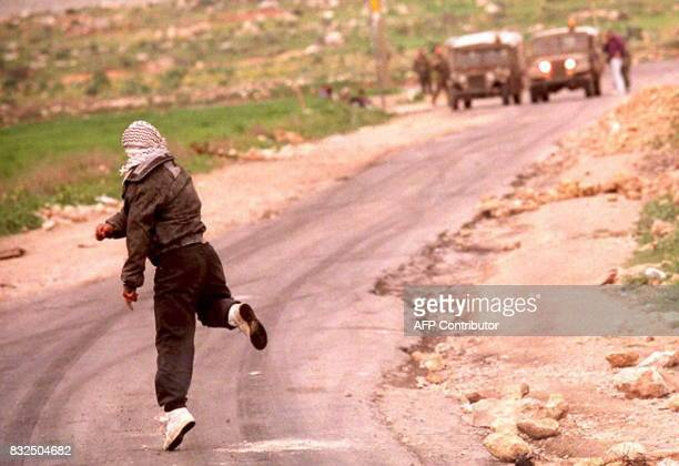 A Palestinian youth throws stone at an Israeli soldier during clashes in Hebron refugee camp of Al Fawwar 15 February where a Palestinian was shot...
