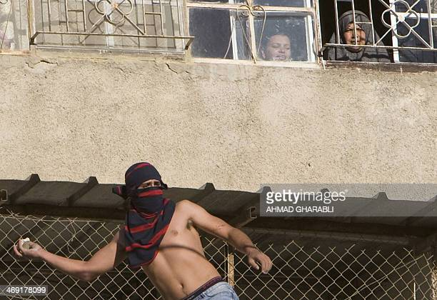 A Palestinian youth throws stones at Israeli security forces during protests in the Arab east Jerusalem neighbourhood of Silwan against Jewish...