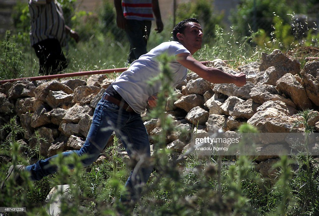 A Palestinian youth throws stones at Israeli soldiers during a protest against the demolition of two houses by Israeli bulldozers on April 30, 2014 in Al-Aroub refugee camp near Hebron. Israeli bulldozers backed by army troops on Wednesday demolished two houses in the Al-Aroub refugee camp near the West Bank city of Al-Khalil (Hebron).