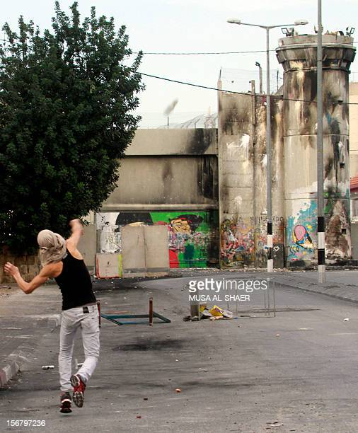 A Palestinian youth throws stones towards an Israeli army tower during clashes with Israeli forces at the main entrance of the West Bank city of...